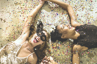 Two young women lying on a carpet surrounded by fallen confetti. - MINF06718