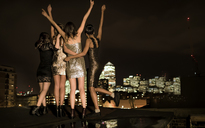 Group of young women standing on a rooftop celebrating. - MINF06724