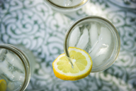 Outdoors in summer. Making lemonade. Overhead shot of lemonade glasses with a fresh slice of lemon in the edge of the glass.  Organic lemonade drinks. - MINF06745