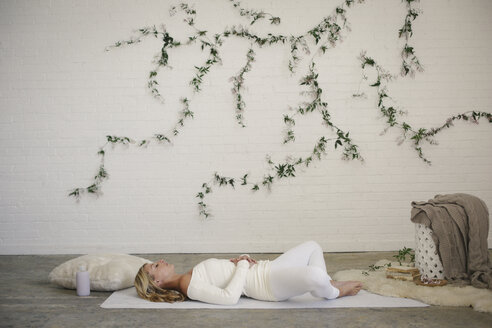 A blonde woman in a white leotard and leggings, lying on a white mat in a room. A creeper plant on the wall behind her. - MINF06783