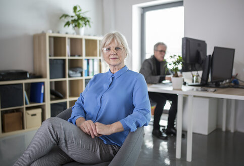 Senior businesswoman sitting in office with colleague working behind her - AWF00178