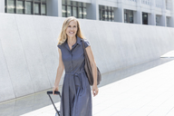 Smiling blond businesswoman with wheeled luggage - TCF05523
