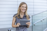 Smiling blond businesswoman using tablet - TCF05526
