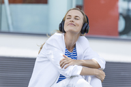 Smiling blond businesswoman with closed eyes, listing music, earphones - TCF05541