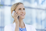 Smiling blond businesswoman using smartphone - TCF05550
