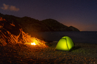Spain, Catalonia, Costa Brava, green tent and camp fire at night - AFVF01375