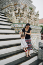 Thailand, Bangkok, Wat Arun, Mother and daughter visiting the Buddhist temple walking downstairs - GEM02253