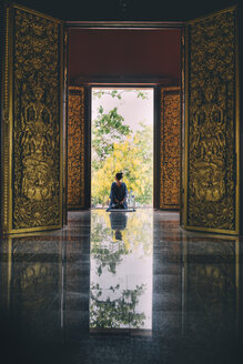 Thailand, Chiang Mai, Woman at the gates of the Wat Rajamontean Buddhist temple - GEM02261