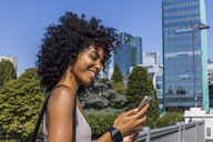 Germany, Frankfurt, smiling young woman with curly hair looking at cell phone - TCF05574