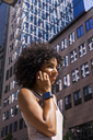 Germany, Frankfurt, portrait of smiling young woman with smartwatch on the phone - TCF05583