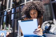 Young woman with curly using tablet in the city - TCF05586