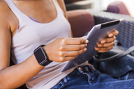Young woman with smartwatch sitting at sidewalk cafe using digital tablet, close-up - TCF05589