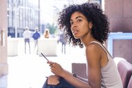 Portrait of young woman with digital tablet sitting at sidewalk cafe watching something - TCF05592