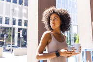 Portrait of young woman with coffee to go and cell phone watching something - TCF05595