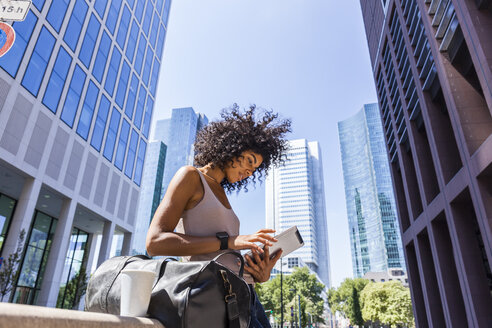 Germany, Frankfurt, young woman with travelling bag and coffee to go using tablet in the city - TCF05598