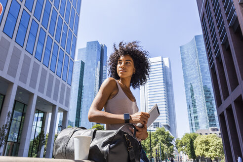 Germany, Frankfurt, portrait of young woman with travelling bag, tablet and coffee to go in the city - TCF05601