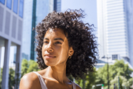 Germany, Frankfurt, portrait of content young woman with curly hair - TCF05604