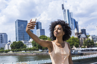Germany, Frankfurt, portrait of content young woman with curly hair taking selfie in front of skyline - TCF05625