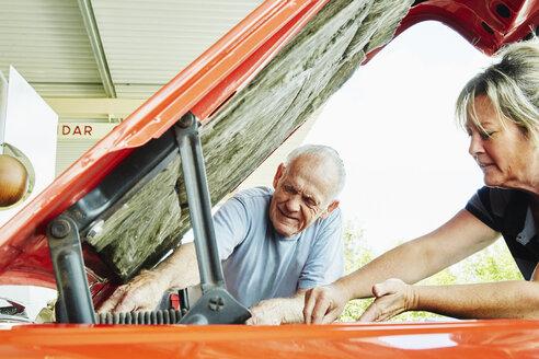 Mature woman and senior man repairing a car, looking under bonnet. - MINF07212