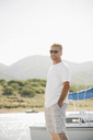 Blond man wearing sunglasses standing on a jetty. - MINF07443