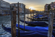 Gondolas moored on a canal in Venice, Italy, at sunrise. - MINF07485