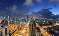 Cityscape of Dubai, United Arab Emirates at dusk, with the Burj Khalifa and other skyscrapers and illuminated highway in the centre. - MINF07506