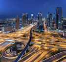 Cityscape of Dubai, United Arab Emirates at dusk, with skyscrapers and illuminated highways in the foreground. - MINF07515