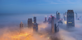 Cityscape with illuminated skyscrapers above the clouds in Dubai, United Arab Emirates at dusk. - MINF07533