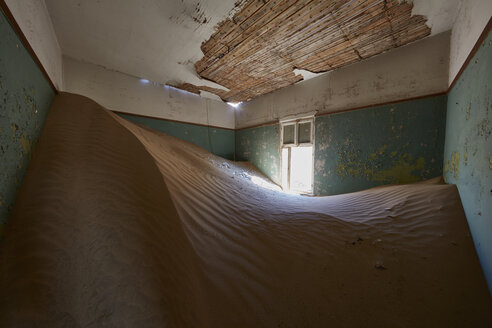 A view of a room in a derelict building full of sand. - MINF07599