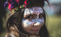 Young woman at a summer music festival face painted, wearing feather headdress, looking at camera. - MINF07623