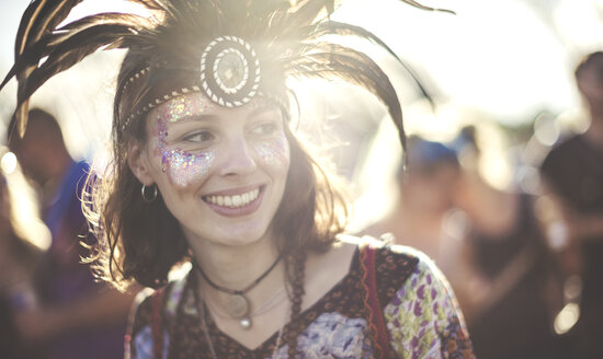 Young woman at a summer music festival wearing feather headdress and face painted, smiling. - MINF07629