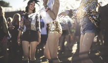 Young woman at a summer music festival wearing golden sequinned hot pants, dancing among the crowd. - MINF07632
