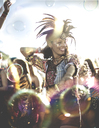 Young woman at a summer music festival wearing feather headdress, dancing among the crowd. - MINF07635