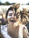 Young woman with long brown hair at a summer music festival face painted, smiling at camera. - MINF07638