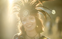 Young woman at a summer music festival wearing feather headdress and face painted, smiling at camera. - MINF07644
