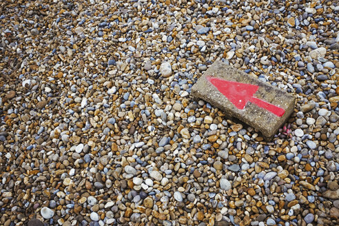 High angle view of red arrow painted on stone lying on pebble beach. - MINF07674