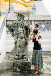 Thailand, Bangkok, mother and daughter at a statue in the Grand Palace - GEM02277