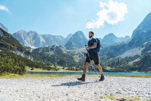 Austria, Tyrol, Man hiking at Seebensee Lake - DIGF04736