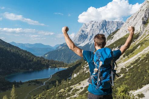 Austria, Tyrol, Hiker with backpack, raising arms, looking at Lake Seebensee - DIGF04760