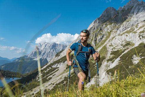 Austria, Tyrol, Young man hiking in the maountains at Lake Seebensee - DIGF04766