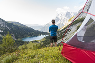 Austria, Tyrol, Hiker standing at his tent in the mountains,  looking at Lake Seebensee - DIGF04787