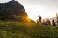 Austria, Tyrol, Hiker with backpack hiking in meadow at sunset - DIGF04799