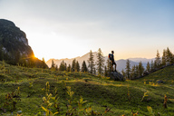 Austria, Tyrol, Hiker with backpack standing on rock, watching sunset - DIGF04802