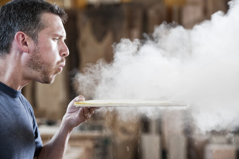 Caucasian man factory worker blowing sanding dust off a wooden piece in a woodworking factory. - MINF07946