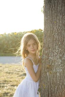 Girl standing on tree trunk at summer evening - LVF07390
