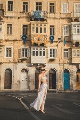 Teenage girl weraing long skirt and bikini top, posing in the street - ACPF00214