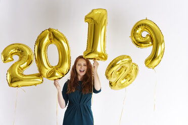Portrait of happy young woman with golden balloons forming the date '2019' - ABIF00880