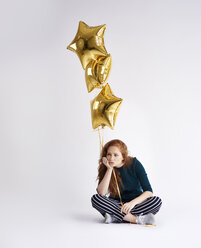 Portrait of young woman with three golden star-shaped balloons - ABIF00883