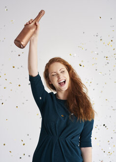 Portrait of happy young woman with bottle of champagne at shower of confetti - ABIF00886