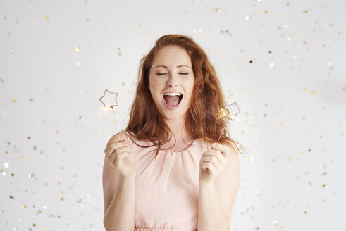 Portrait of shouting young woman with two sparklers - ABIF00889